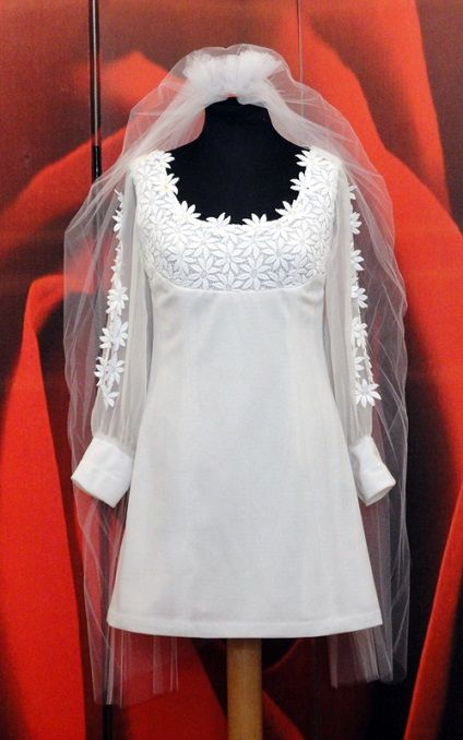 A circa 1970 mini wedding dress. Bodice in lace daisies macrame, adorned with iridescent teardrop crystals. Long chiffon open sleeve hemmed with lace daisies macrame. Wedding dress and photo Vintachic