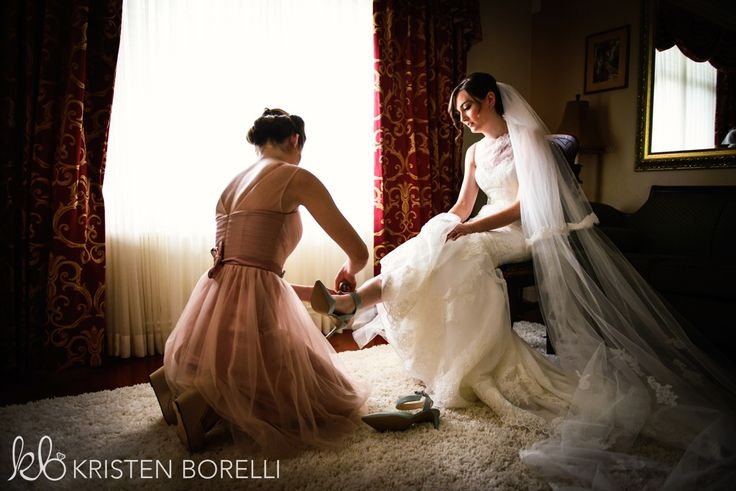 Bride's sister helping put her pastel blue wedding shoes on. Bride wearing Enzoani gown with a cathredal veil.