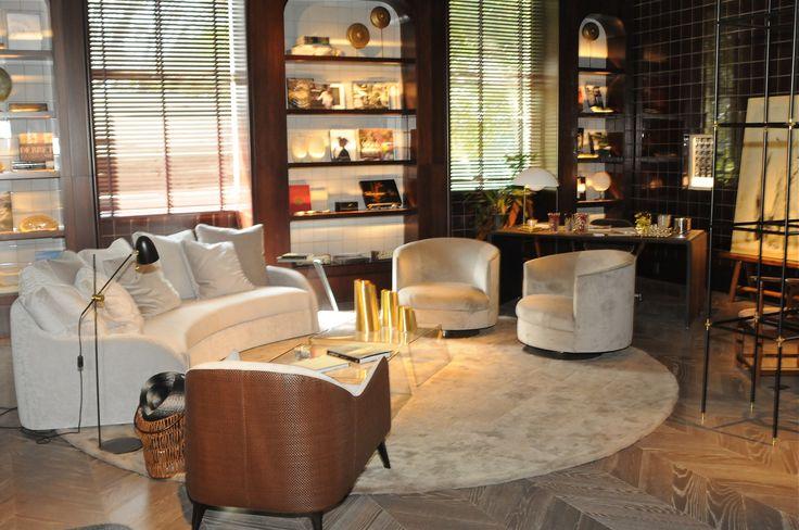 Casa Cor 30 anos | Almoço de sexta - sofá curvo, poltronas bege, prateleiras decorativas, luminárias de chão