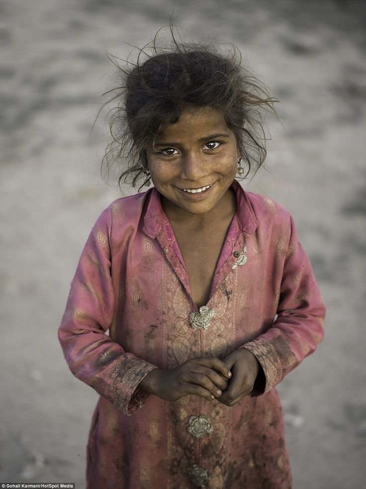 A young girl dressed in muddy clothes and living in the slums of Sahiwal, but smiling for the camera against the odds
