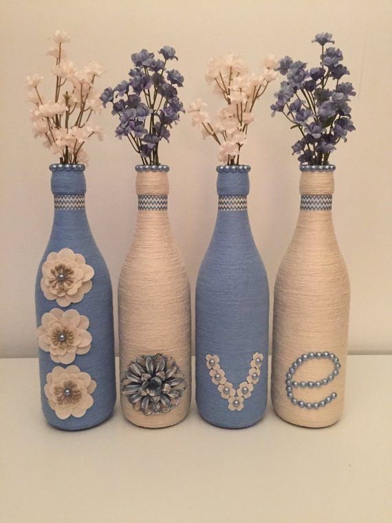 Each bottle is 12 tall and wrapped in neutral twine and blue yarn. Embellishments include burlap butterflies, white and blue adhesive pearls, grey/blue metal flower, small burlap flowers, white and blue decorative flowers. These bottles can be used as vases, centerpieces for a