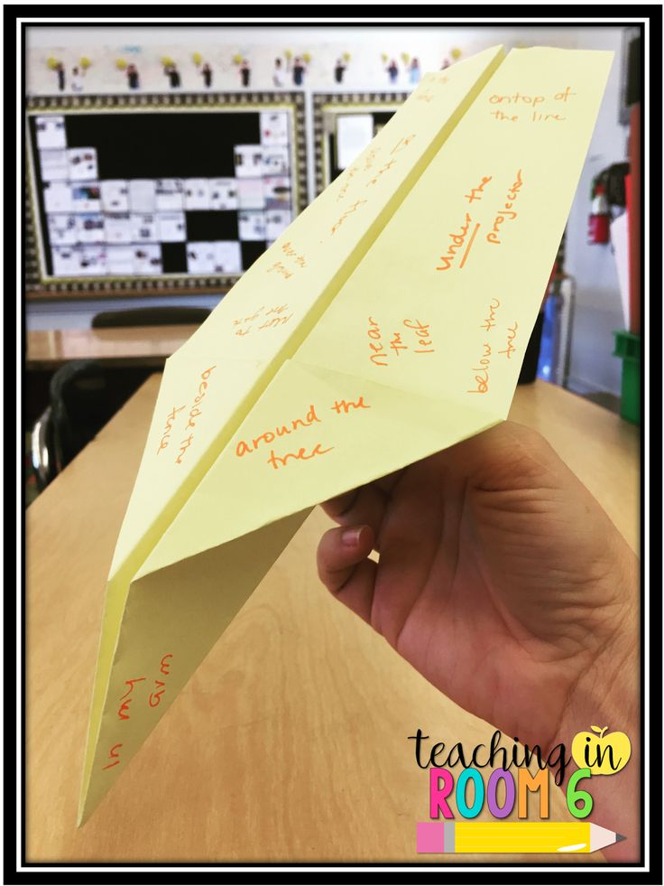 Students write prepositional phrases on the paper airplane as it landed on the floor.