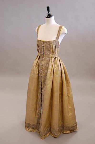 A cloth of gold regional dress or Sarafan and bonnet, Russian, mid 19th century, pniafore-style with pleated bodice, filligree buttons to the front closure, trimmed with broad bands of bobbin lace, the bonnet crown and curved worked with pearlised beaded blooms