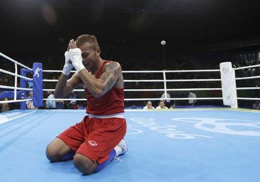 Thailand's Amnat Ruenroeng prays after winning a match against Argentina's Perrin Ignacio during a men's lightweight 60-kg preliminary boxing match at the 2016 Summer Olympics in Rio de Janeiro, Brazil, Sunday, Aug. 7, 2016. (AP Photo/Frank Franklin II)
