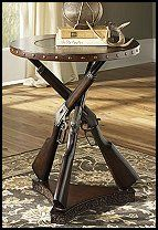 Old Western Rifle Accent Table. This piece offers a distinct yet appealing wood top with an etched brass inlay of a cowboy design along with a faux rifle base. With everything this one-of-a-kind accent table has to offer, its sure to be a topic of conversation among guests.