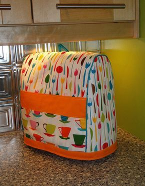 pattern online to make a KitchenAid stand mixer cover. She adds: I added a little pull tab/loop at the top of the cover, lined the cover, and added side pockets to fit the attachments. I also added an extra, extra wide bias tape strip at the bottom in order to make it an inch longer. I would definitely add another inch or two to the length of the cover if I were to make it again.