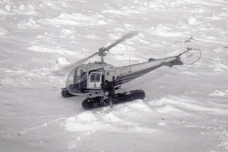 Ontario Hydro Helicopter on Ice Covered Lake Huron, February 1971. The person climbing onto the helicopter pontoon is me (Joe Hollick).  We had landed on the ice in front of the proposed site of Bruce Generating Station, Ontario Canada