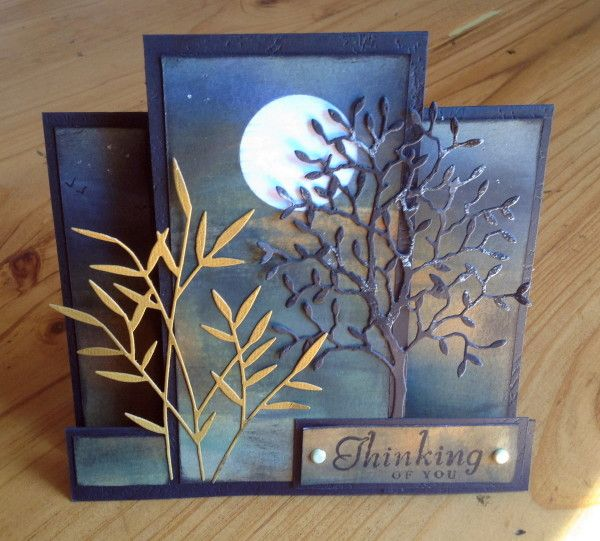 By susie australia at splitcoaststampers. Mask moon on white cardstock panel; sponge with Distress inks. Add little spots of glitter for stars. Cut panel into 3 parts. Attach to a step card base. Die cut tree and bamboo (both Memory Box); add to center panel. Add sentiment.