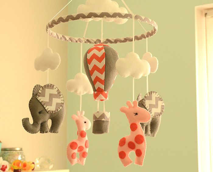Welcome To Flossytots  This Elephant Mobile is MADE TO ORDER    This mobile consists of 2 Elephants in Grey and 2 Giraffes in Blush/ Coral made with premium wool blend felt. Above each elephant is a cloud. Hanging in the centre is a hot air balloon using the same colours used on the elephants.  If you prefer the hoop covered with coral chevron just send a convo!  These mobiles are original Flossytots designs and are carefully cut and handstitched with lots of care and attention to detail…