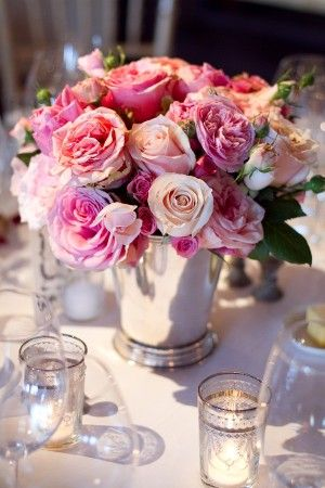 "The guest book table will feature a trio of silver mint julep cups filled with purple hydrangeas, ""blue moon"" spray roses, lavender stock flowers, and grey dusty miller."