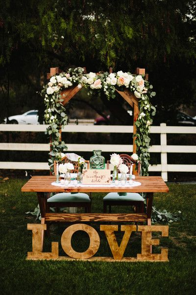 "Outdoor sweetheart table idea - wooden arch draped with eucalyptus and pink + white blooms, wooden table and ""LOVE"" letters  {Cory Kendra Photography}"