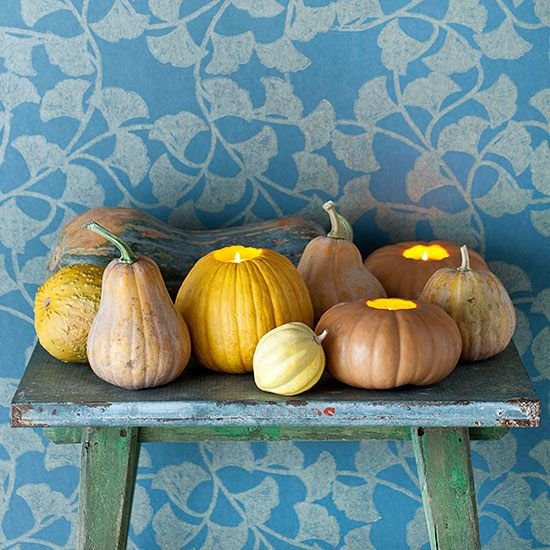 Jack-o-lanterns add a spark to your autumn-inspired decor, but this time, the faces and fancy carvings aren't necessary. Simply cut a hole in the top of a pumpkin, scoop out the insides, and place a candle inside the cavity to create a warm fall light. Try different sizes of pumpkins and surround them with gourds and other pumpkins to complete the arrangement.