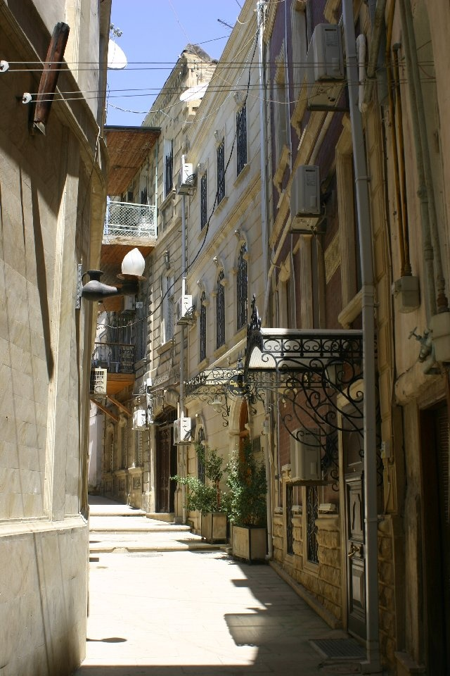 Old City alley, Baku, Azerbaijan. Baku, the capital and commercial hub of Azerbaijan, is a low-lying city with coastline along the Caspian Sea. It's famed for its medieval walled old city, which contains the Palace of the Shirvanshahs, a vast royal complex, and the iconic stone Maiden Tower.