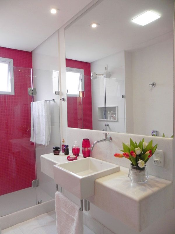 A parede de pastilhas vermelhas foi um pedido da moradora, por isso, a arquiteta Lorrayne Zucolotto optou por elementos brancos para compor o banheiro. Um dos detalhes interessantes do ambiente é o material da bancada – um mármore branco – que se repete nos rodapés.