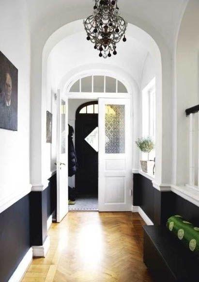 Narrow hallway styling. black chandy & wainscotting.
