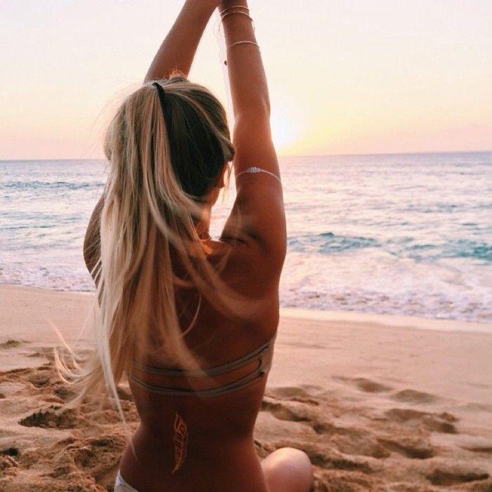 Chica con los brazos alzados en la playa
