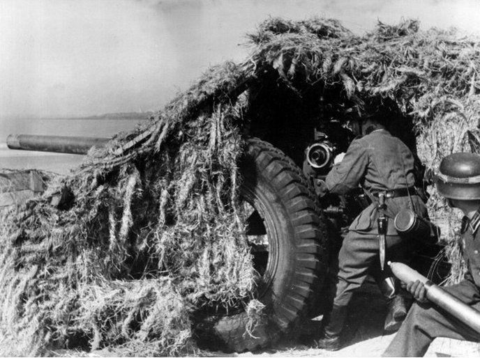 German artillerymen shooting with a camouflaged medium-calibre gun. France, September 1943