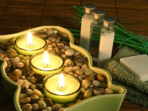 Grouping votive candles in a larger dish and filling it with pebbles can bring the spa to anyone's bathroom.