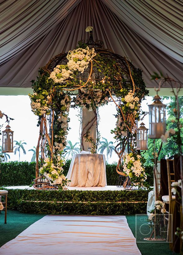 An enchanted wedding altar features a chuppah overgrown with vines and beautiful flowering