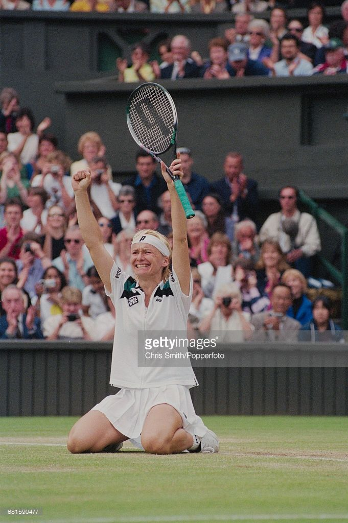 Czech tennis player Jana Novotna kneels on the court and raises her arms in the air in celebration after winning the final of the Women's Singles tournament against Nathalie Tauziat of France, 6-4, 7-6 to become champion at the Wimbledon Lawn Tennis Championships at the All England Lawn Tennis Club in Wimbledon, London on 4th July 1998. (Photo by Chris Smith/Popperfoto/Getty Images)
