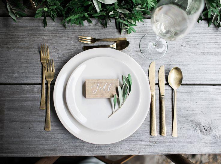 Je tafel setting heeft echt niet veel poespas nodig, zo mooi kan het zijn met goud bestek en prachtig gekalligrafeerde naamkaartjes. Foto: Bianca Rijkenbarg