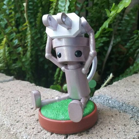 Custom chibi robo amiibo repainted to rose gold with a white plug. Cute little design on the plug seals the deal as the prettiest chibi robo amiibo out there!  Hand-painted and then varnished for long-lasting display.  Great for any Nintendo fan or amiibo collector looking to add a unique piece to their shelf. Custom amiibo also make great gamer gifts!  Thanks for looking and please browse my shop to see my other customs. If you would like a custom that you do not see, please feel free to…