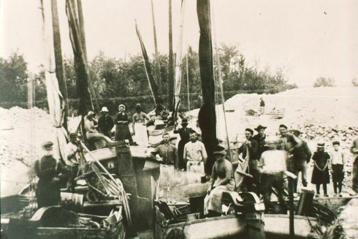 """Skûtsjes (""""Modderschuiten"""") gelegen bij de terp te Britsum, waarmee de afgegraven terpgrond naar de zandgronden elders in de provincie werd vervoerd (foto circa 1915, fotonummer LWL00226)."""