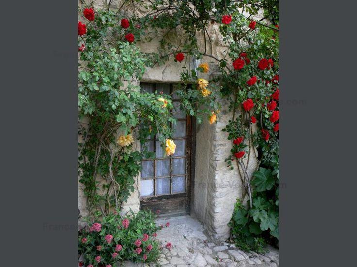 Dauphin: Deur van een huis versierd met rode en gele rozen (klimrozen)…