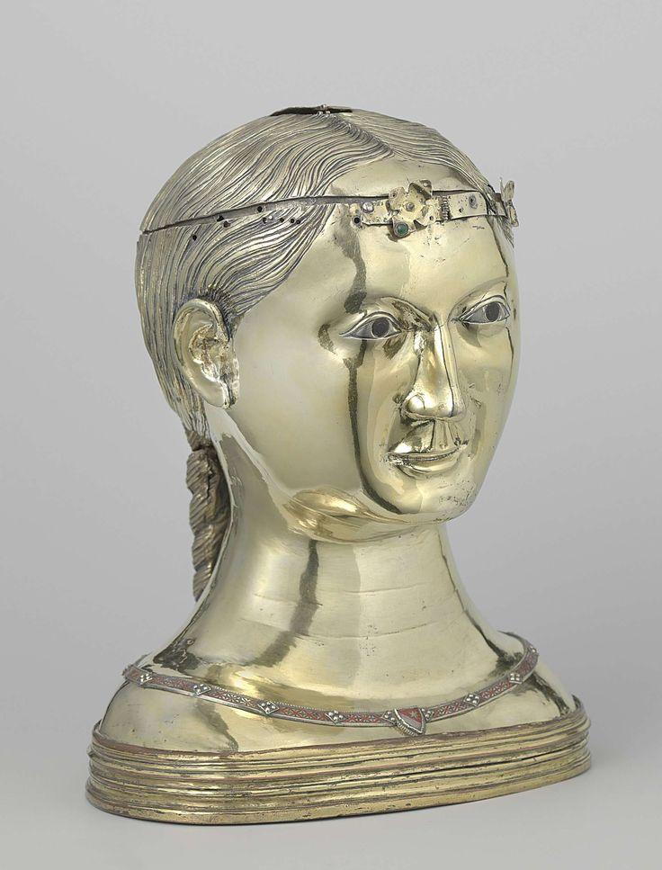 Anonymous | Reliquary bust of Saint Thekla, Anonymous, c. 1290 - c. 1300 | Reliekbuste van verguld zilver en email, voorstellende de heilige Thekla. Het haar is aan de achterzijde in twee vlechten verdeeld. Om de hals, langs de rand van het gewaad, een ketting met rood email en, aan de voorzijde, een wapenschild. Bruin geëmailleerde ogen tegen blank-zilveren oogbol. Van de haarband zijn enkele resten over. Op een basis van verguld koper.