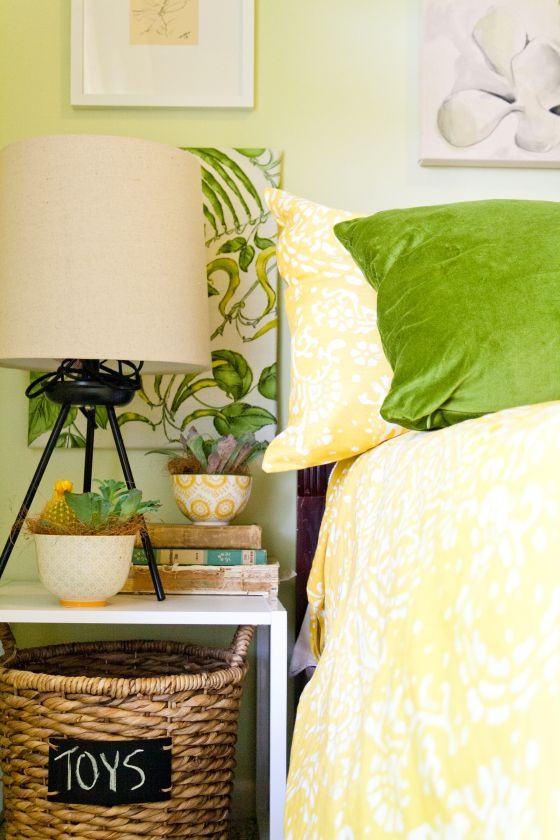 nightstand styling, framing fabric as art, green and yellow botanical bedroom, budget room makeover, yellow bedding, tripod lamp, toy bin