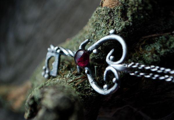 Srebrna zawieszka w kształcie klucza, z motywami serca tu i ówdzie :) W centralnym punkcie umieściłam granat. / Silver pendant in a shape of the key with some hearts. The stone in the center is a garnet.