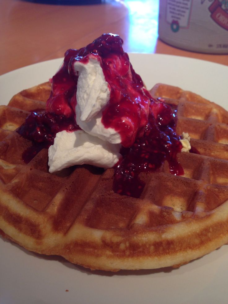 Crispy waffles with almond flavored whipped cream and raspberry sauce.