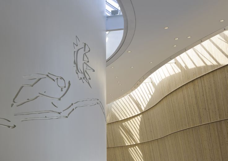 The decoration of the foyer in Culture Centre of Greenland is – as well as the building – a reference to the surrounding nature and Greenlandic culture. The Greenlandic artist Buuti Pedersen has created the relief based on the old myth of the sun and the moon called Malina & Aningaaq. The relief is carved directly into the wall. #architecture #art #greenland #culture