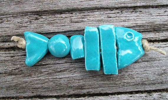 This is such a fun piece for a necklace or bracelet design. Ceramic fish bonz has 6 seperate pieces to complete the fish. Head, 3 straight pieces, a small round bead and the tail. A hole goes through each piece. Together it measures 2 long. It is glazed a shiny turquoise color. Bead has been published in Step by Step Wire Magazine…