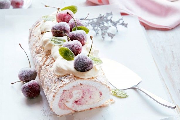 For the perfect Christmas dessert, try this heavenly pavlova roll topped with frosted cherries and mint leaves.