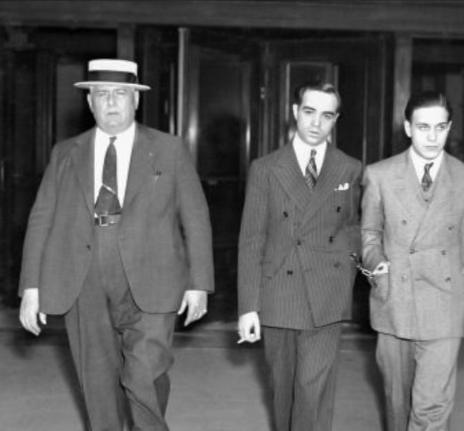 June 5, 1937 - Handcuffed together are James Plumeri aka Jimmy Doyle (middle) and Johnny Diodorno as they leave court after session. There is nothing delicate about Racketeer Plumeri who is on trial for conducting a trucking shakedown that earned him a small fortune.