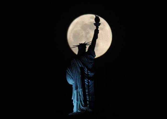 Super moon with Statue of Liberty    We'll pretend this is from NYC but the full moon rises behind a Statue of Liberty replica atop of a hotel in Kosovo's capital Pristina.