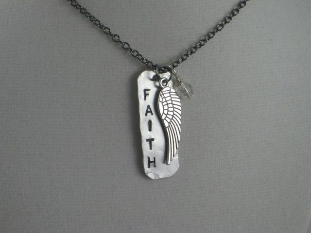 FAITH - So many meanings. What does FAITH mean to you?  The Brand New rustic FAITH with WING Necklace features a 1 1/2 x 1/2 inch long thin light weight aluminum tag hand distressed and hand hammered with FAITH hand stamped (using a very heavy hammer strike to emphasize the letters) vertically down one side with a 1 1/2 inch long pewter wing dangling off to the other side. The FAITH with WING Necklace will arrive on a long 24 inch gunmetal chain making it perfect as a layering piece! If you…