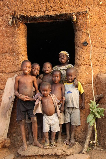Big smiles - Kids in front of the entrance to their home - Benin, Africa