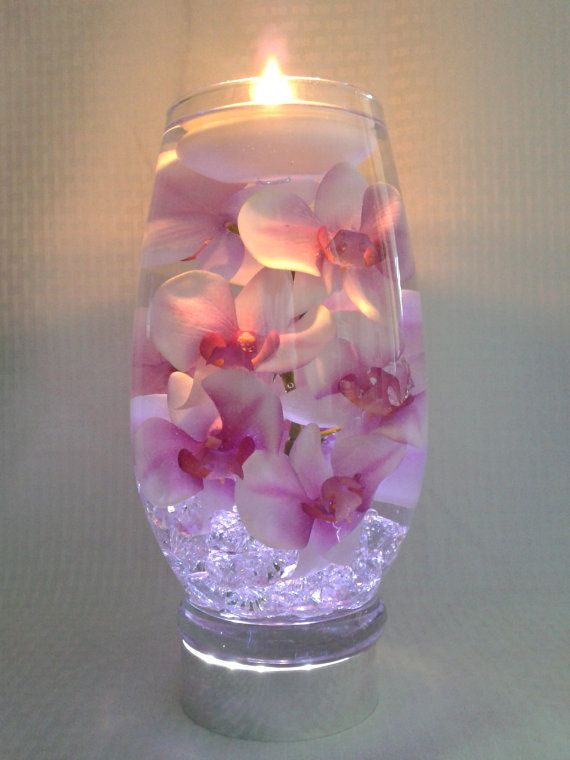 Pink orchids with purple centers float in a 12 inch glass vase filled with water perfect for wedding reception centerpieces or home decor