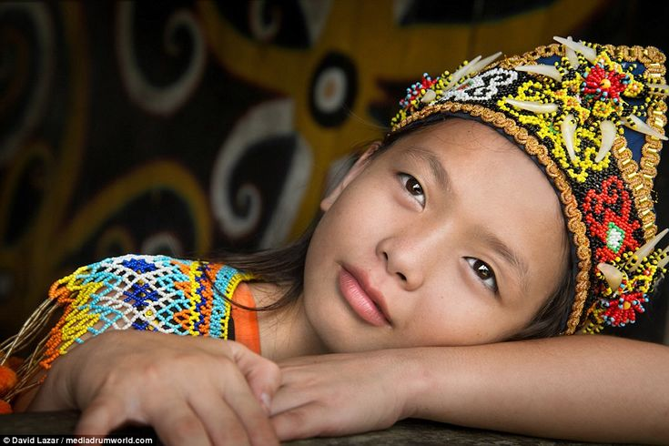 An Indonesian girl is pictured dressed in a traditional outfit, with an intricately beaded headpiece adorned with shells
