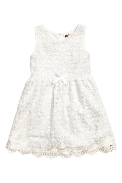 Een mouwloze kanten jurk van zachte katoenmix met een splitje met een knoop in de nek, een naad in de taille en een aangerimpelde rok. Gevoerd met tricot.