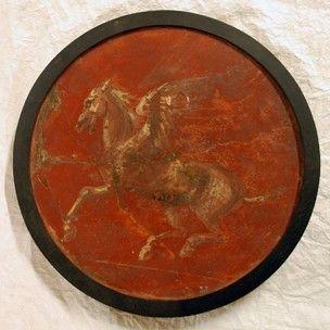 frammento circolare di pittura murale: Pegasus volante a sinistra, dipinta nel IV stile;  violaceo-bruno con riflessi bianchi sul profondo terra rossa.