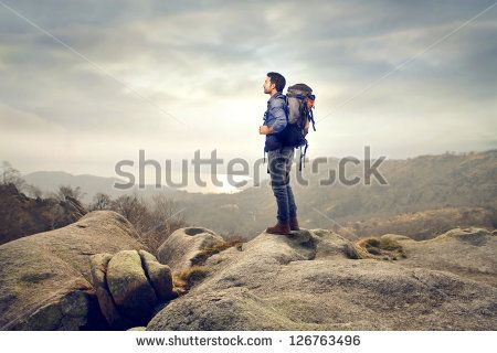 young man with backpack hiking in the mountains