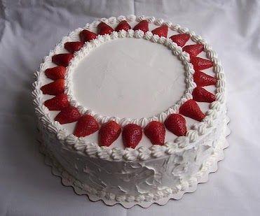 Torta cubierta con merengue italiano y adornada con fresas.
