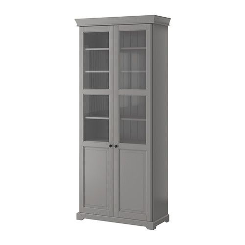 LIATORP Bookcase with glass doors - gray - IKEA - on either side of gray desk on sunroom wall