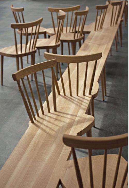 door hout is hier een groot kunst werk gemaakt een sort lange bank met allemaal stoelen erin verwerkt.