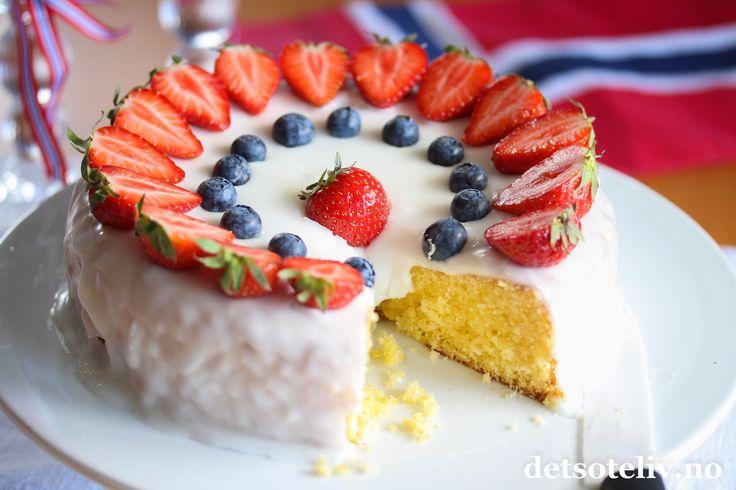 Hei kjære deg! Det er en uke til 17. mai nå og tid for å planlegge kakene du vil lage. Du finner mange tips i kategorien for 17. mai-kaker her på Det søte liv, og i dag skal du få et tips til: Dette er en enkel, men utrolig god sitronkake. Kaken er svært myk og saftig, og har en frisk og deilig smak av sitron. En av de beste formkakene jeg vet om! Med hvit glasur, røde jordbær og blåbær får du lett en vakker kake i rødt, hvitt og blått!