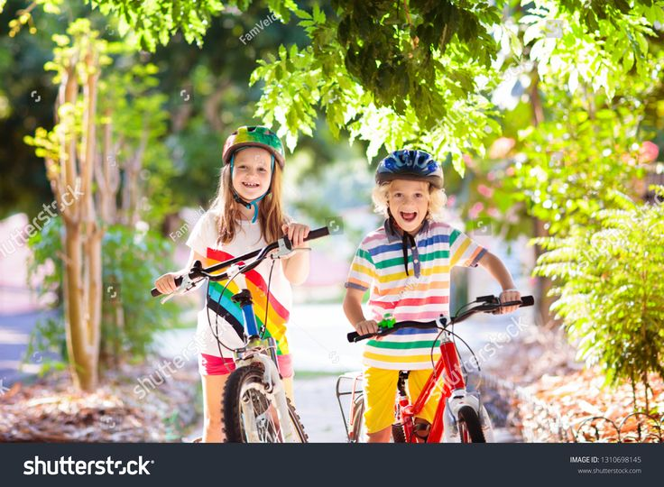 Kids on bike in park. Children going to school wearing safe bicycle helmets. Lit…