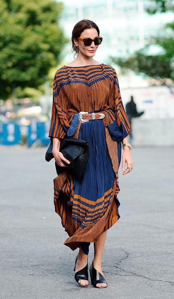 Ece Sukan exibe look com vestido plissado com listras, sandália mule preta, cinto com fivela marrom e clutch preta